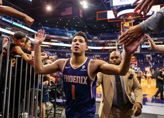Suns guard Devin Booker high-fives fans after hitting a game-winning shot against the Grizzlies on Nov. 4 at Talking Stick Resort Arena.