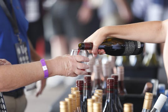 Guests get a pour of wine during the azcentral Wine & Food Experience at WestWorld of Scottsdale, Ariz. on Nov. 4, 2018.