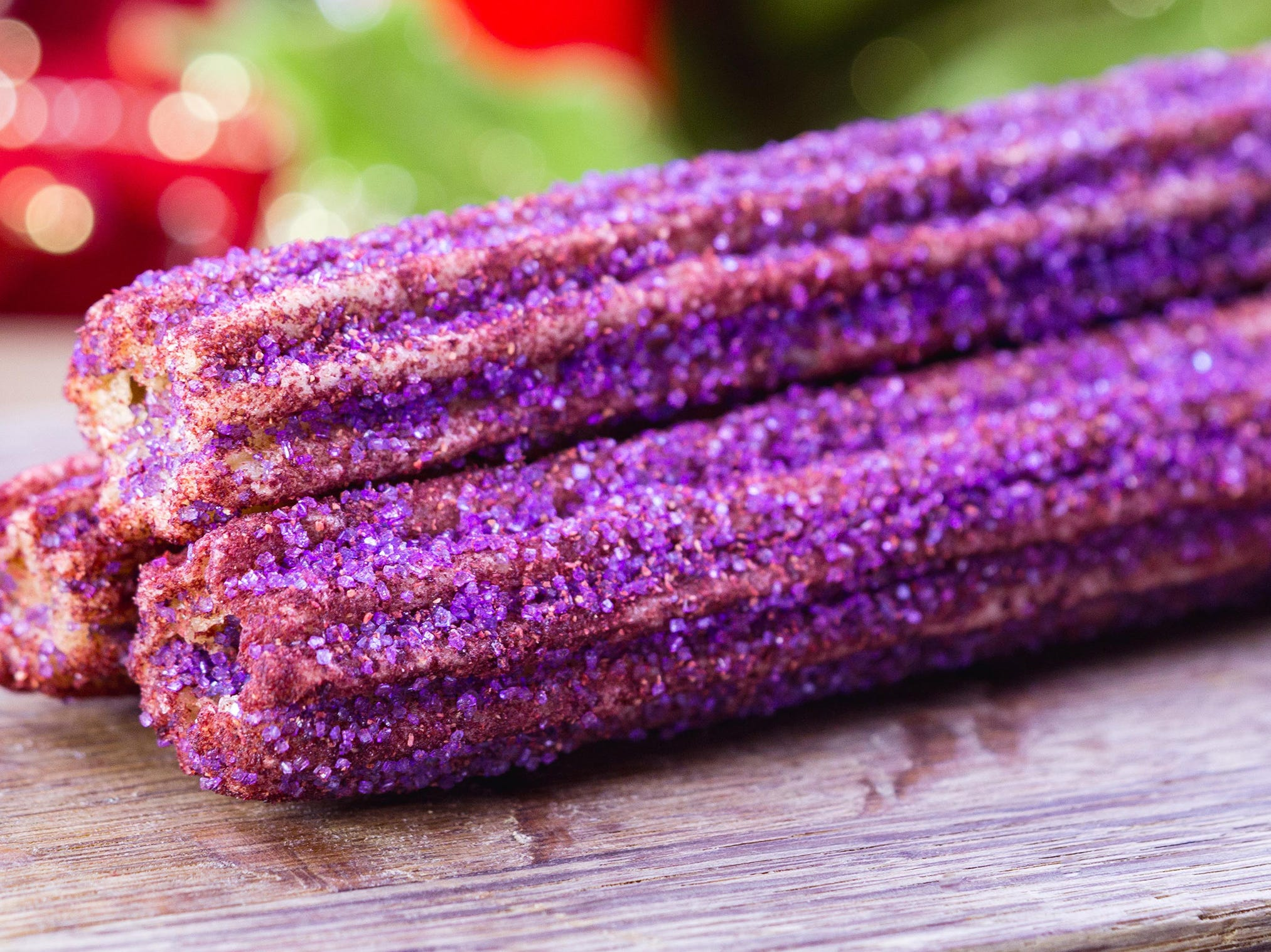 The sugar plum candy churro can be found for a limited time near Haunted Mansion in New Orleans Square at Disneyland park during Holidays at the Disneyland Resort.