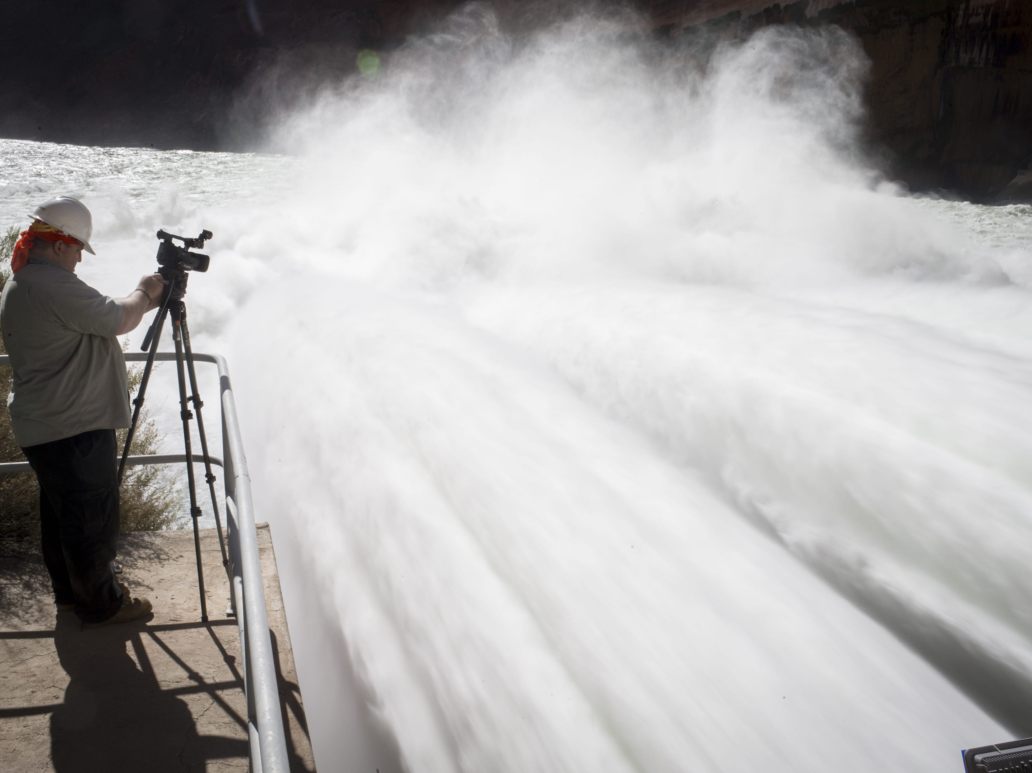 Chris Watt takes a video of water being released from Glen Canyon Dam through a bypass tube on Nov. 5, 2018, during a high-flow experiment.