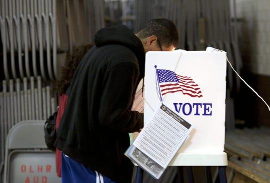 Un joven hispano deposita su voto. Foto archivo.