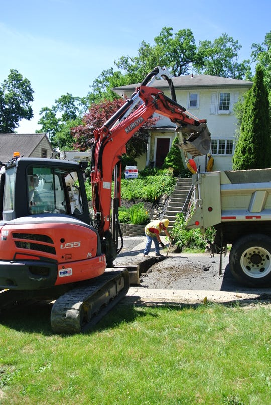 Workers from Central Hudson Gas & Electric dig a trench to allow for the replacement of a service line to a Newburgh home.