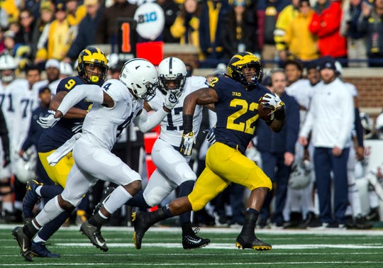 Michigan running back Karan Higdon (22) rushes away from Penn State safety Nick Scott (4) and safety Garrett Taylor (17)  on Saturday. The Wolverines finished the game with 259 rushing yards. (AP Photo/Tony Ding)
