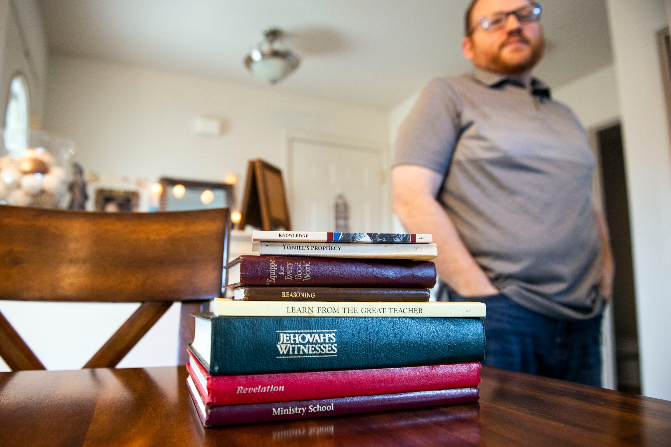 A stack of Jehovah's Witnesses' literature sits on the table as Martin Haugh, an ex-elder at the Red Lion Kingdom Hall, looks over them, Sunday, Oct. 21, 2018. The last straw for Haugh, before leaving the religion, was an email instructing him to discard certain literature. After doing his own research and learning about major contradictions in the faith, Haugh decided to leave. He's now a non-believer.