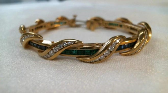 A gold bracelet with sapphires and emeralds is part of an auction of abandoned Nevada property being held online Nov. 5-14, 2018.