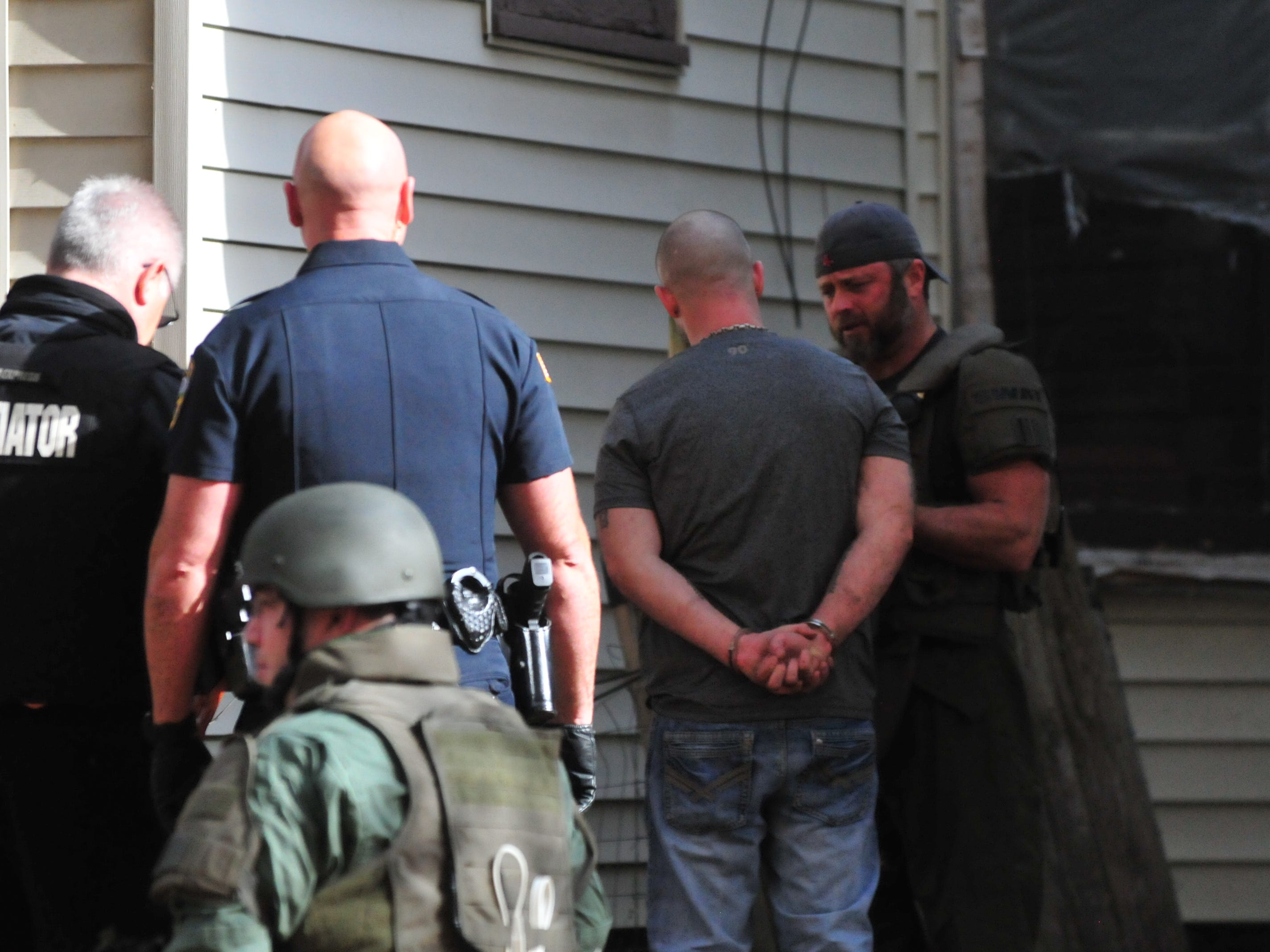 Lt. Scott Crull speaks with Corey Groce after a SWAT raid Monday on North 16th Street.