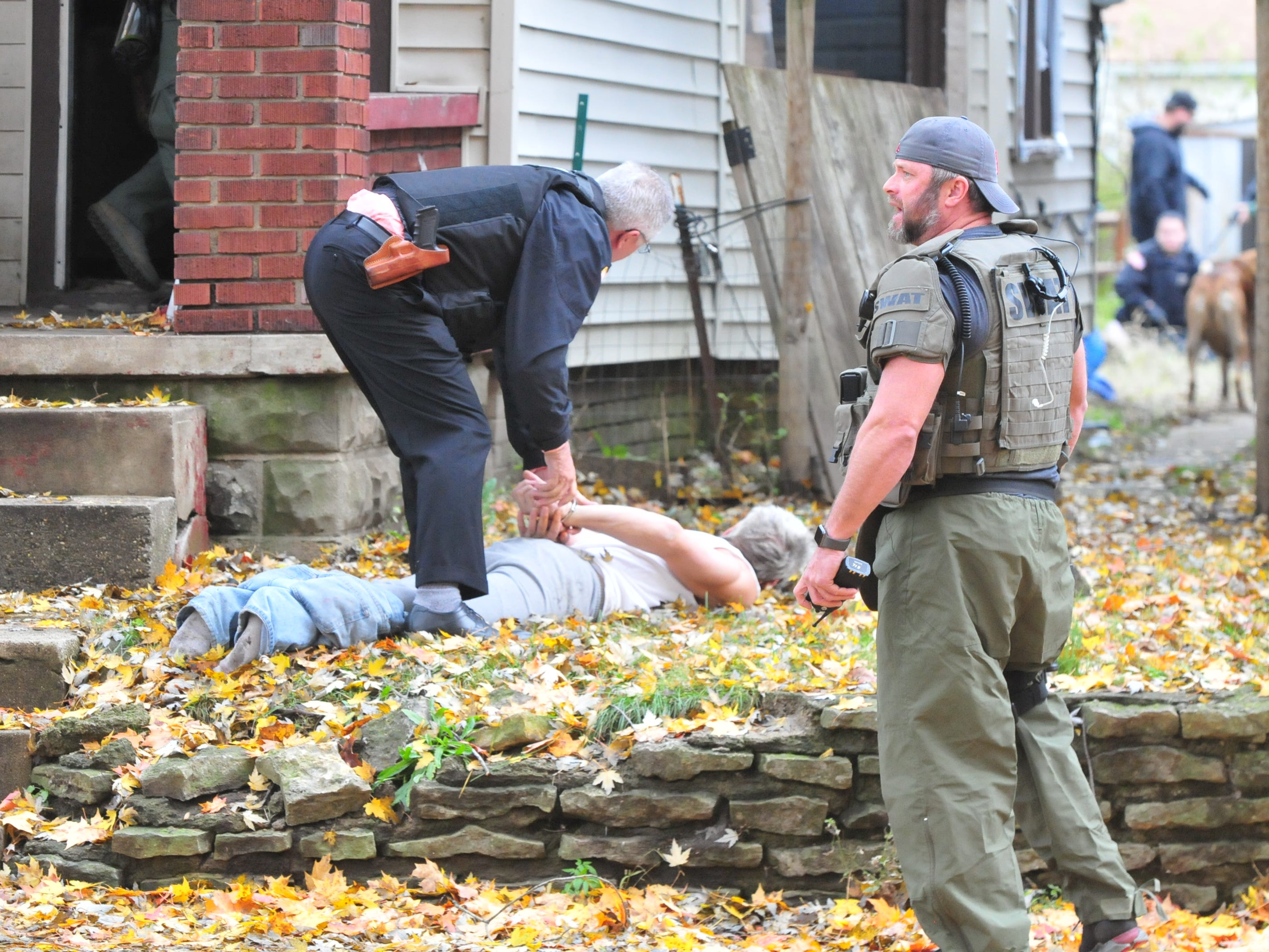 Lt. Donnie Benedict handcuffs James Hamilton as Lt. Scott Crull waits for more suspects to be removed from 219 N. 16th St. during a SWAT raid Monday.
