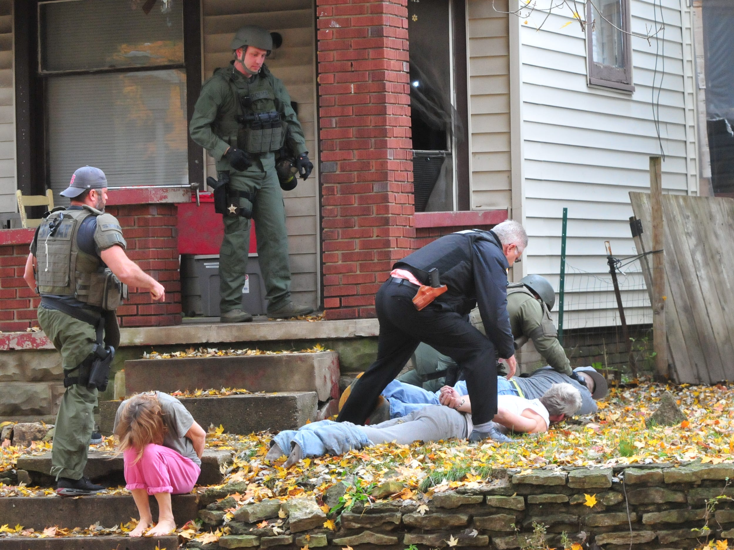 Corey Groce is put on his stomach outside 219 N. 16th St. during a SWAT raid Monday.
