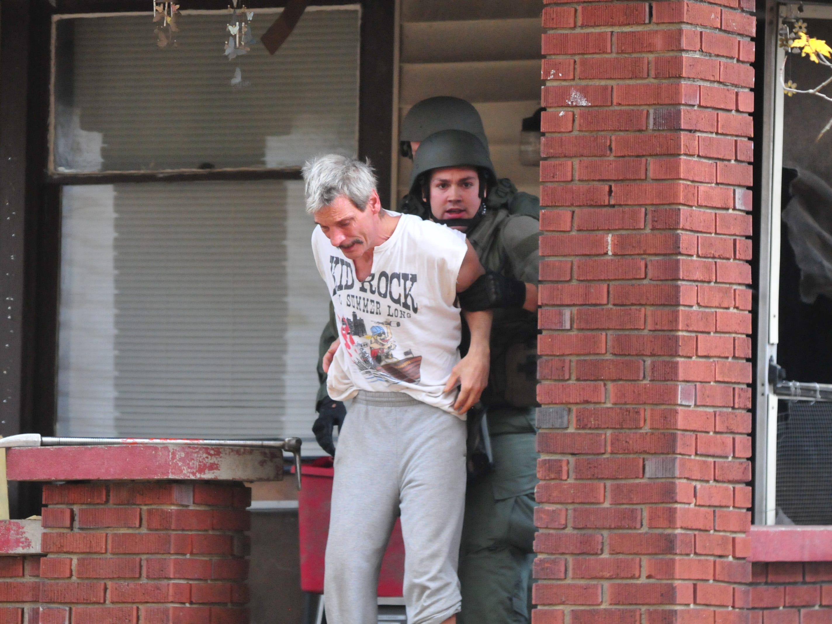 James Hamilton is led by SWAT team members from the house at 219 N. 16th St. on Monday.