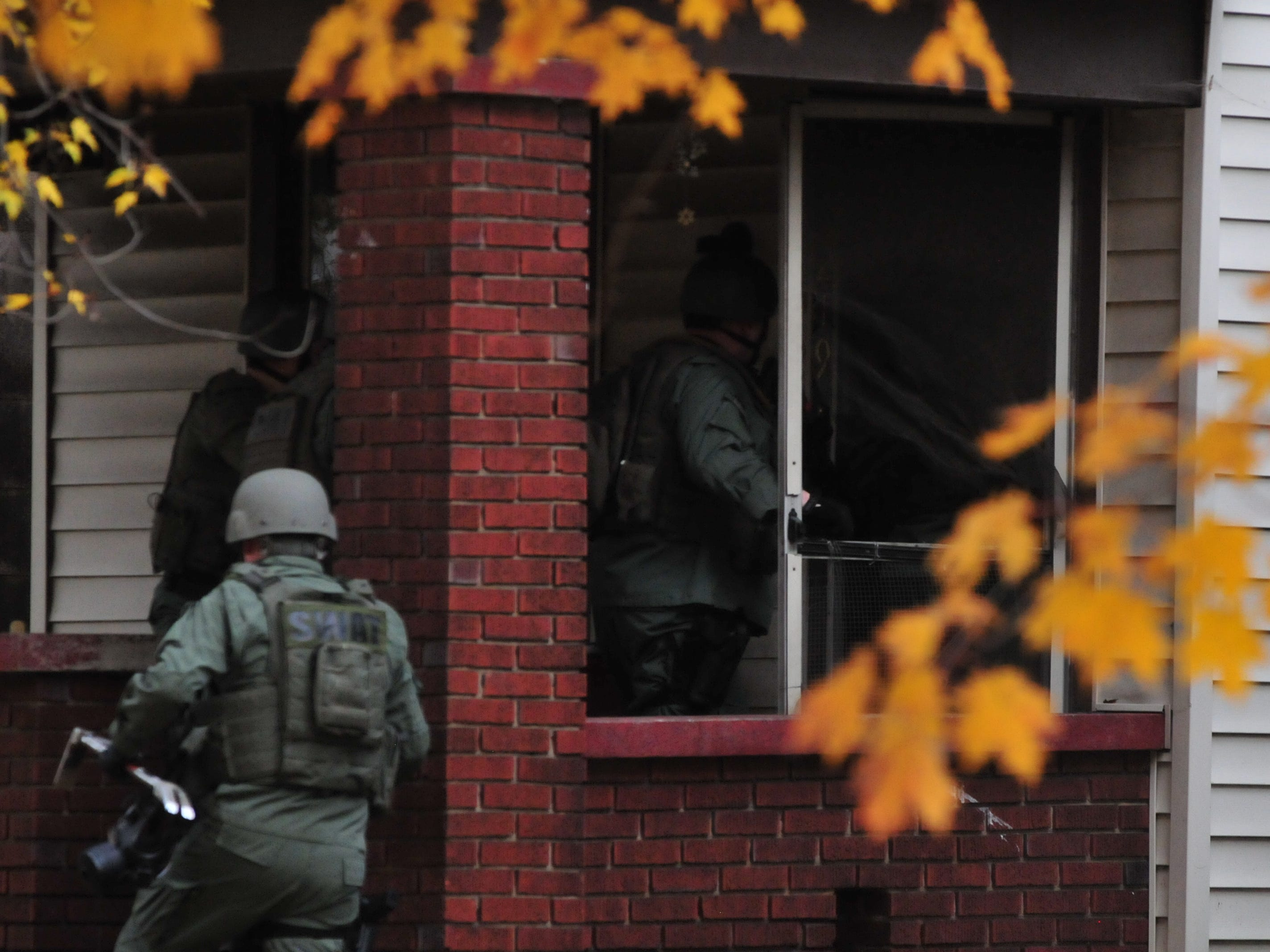 SWAT team members enter 219 N. 16th St. to execute a search warrant Monday.