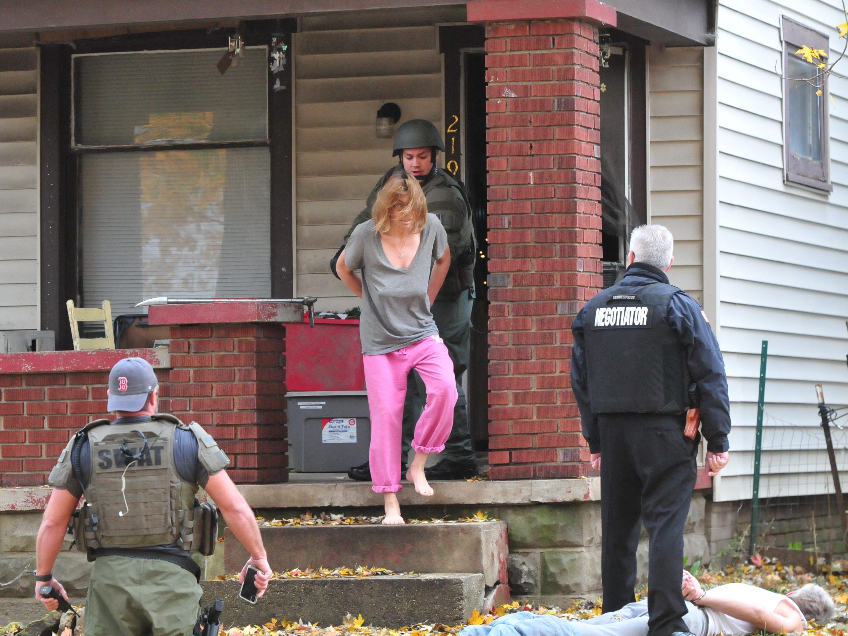 Lorri Davis is led from 219 N. 16th St. during a SWAT raid Monday.
