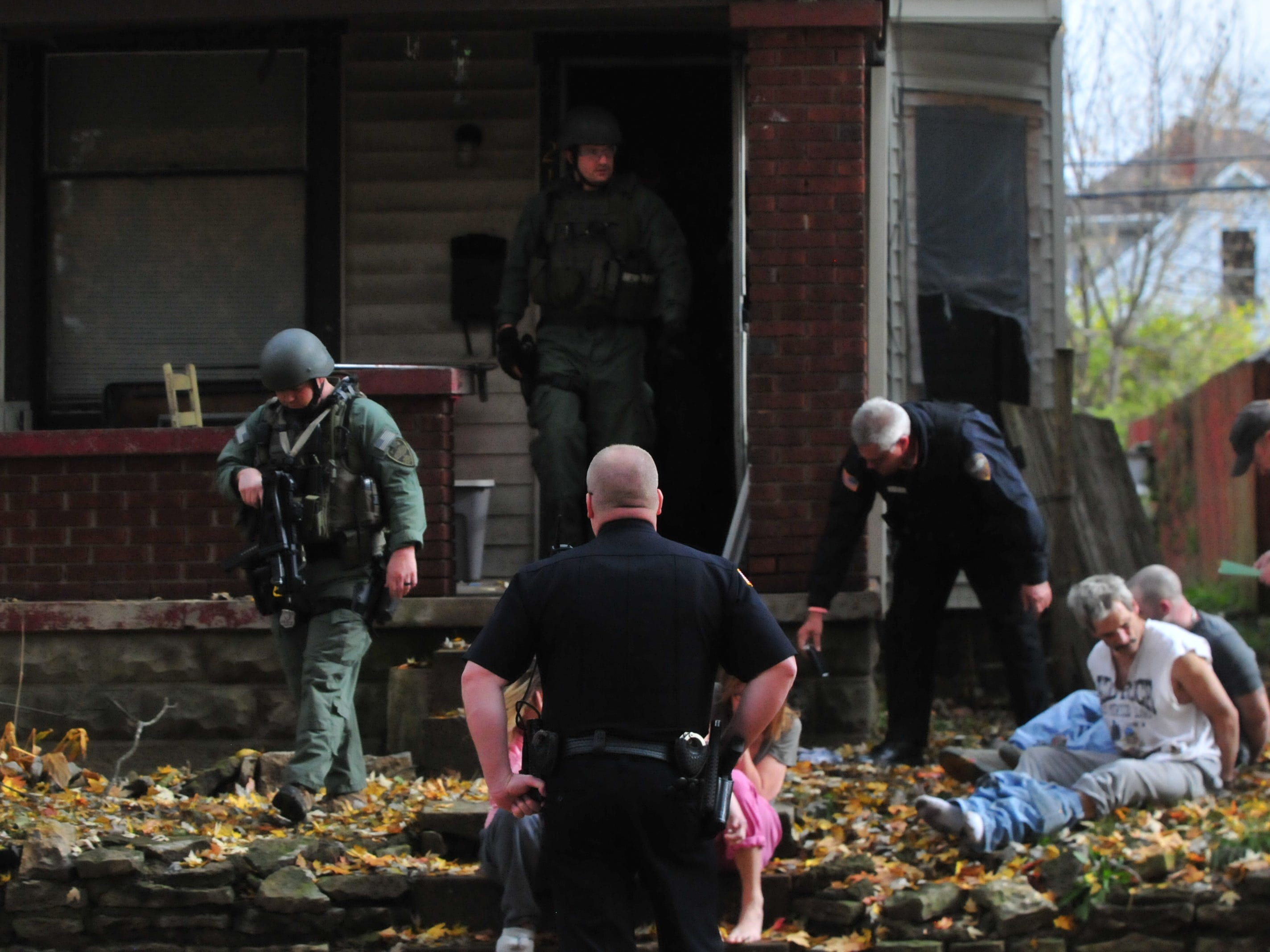 SWAT team members leave 219 N. 16th St. during a raid Monday.