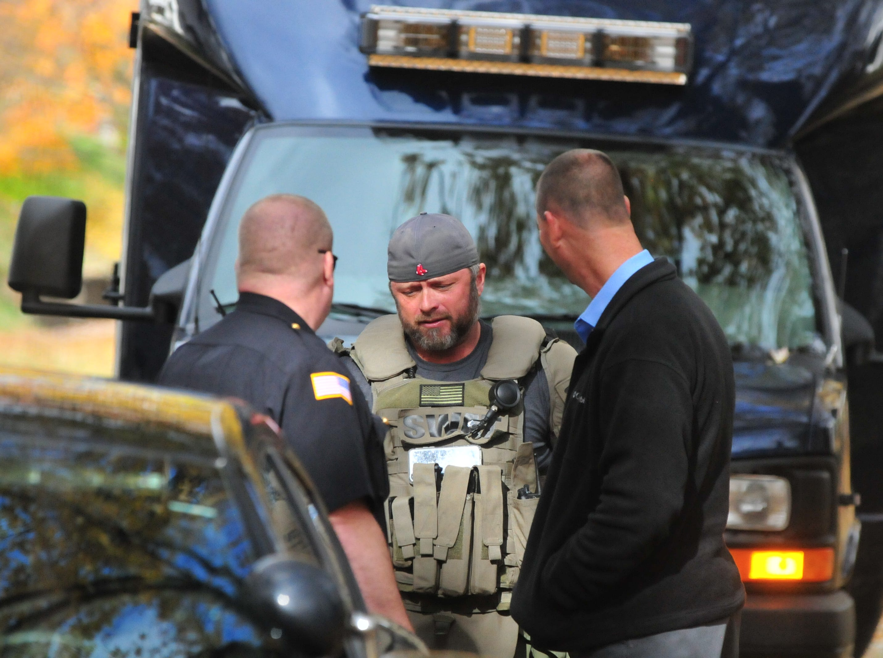 Lt. Scott Crull, commander of the Wayne County Drug Task Force and the SWAT team, talks with Major Jon Bales and Capt. Curt Leverton after Monday's SWAT raid on North 16th Street.