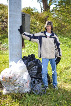 Kellie Fulton, 55, stands with two large trash bags she filled with garbage on Sunday, Nov. 4, 2018. Fulton spent more than three hours on Sunday picking up trash alongside the Phillips Road ramps on Route 104, and says the town won't collect the trash.