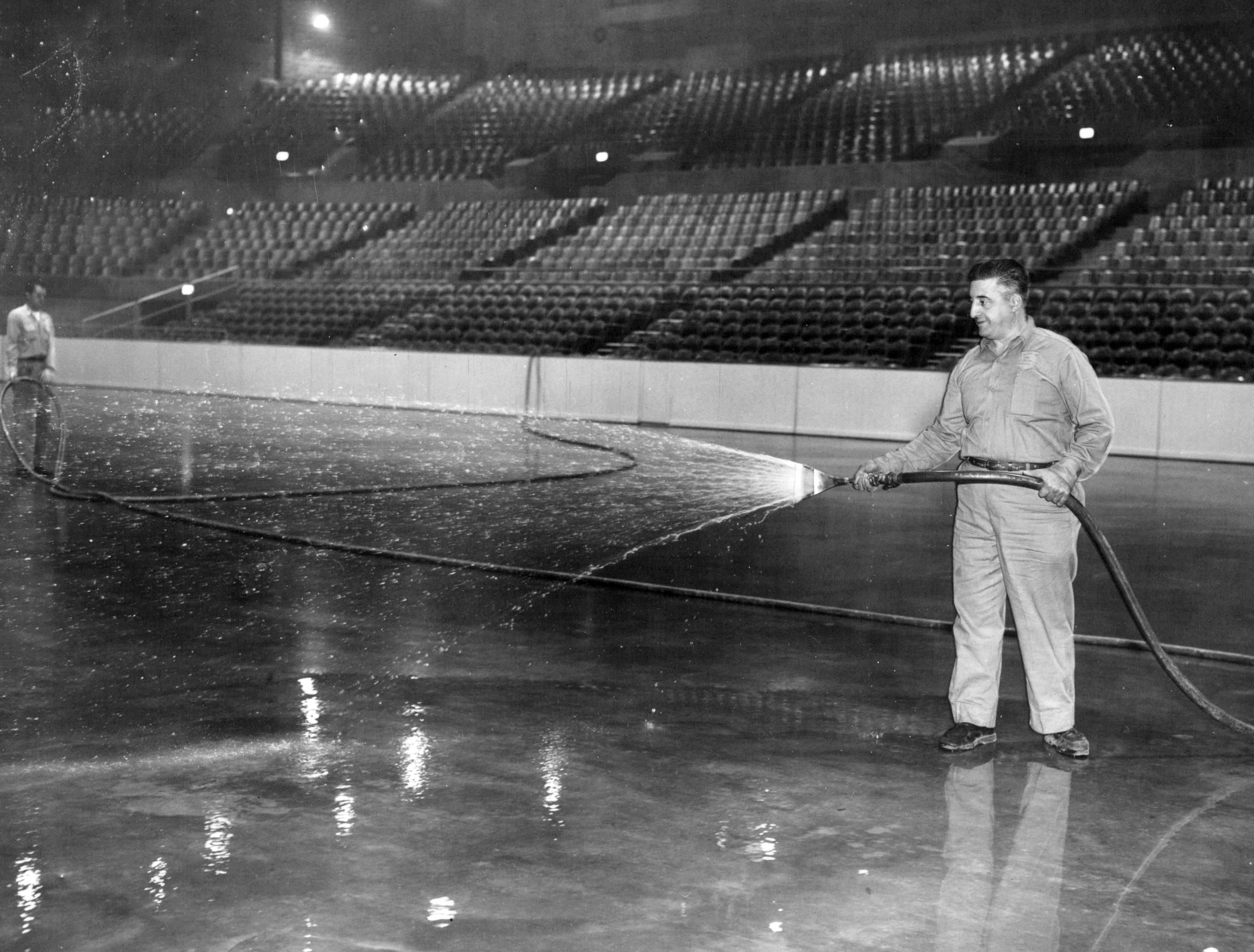 In this photo from 1955, Joseph DiPaulo sprays water in the first trial of ice-making equipment at the Community War Memorial.