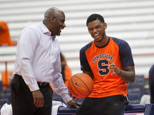 Syracuse's Frank Howard, right, laughs with Syracuse assistant coach Allen Griffin before the team's exhibition against LeMoyne on Oct. 31. Howard could miss the Orange's season opener on Tuesday with an injury.