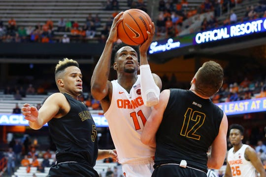 Syracuse forward Oshae Brissett drives to the basket between Michael Wearne, left, and Shane Herrity of St. Rose during the first half of an exhibition game at the Carrier Dome on Oct. 25.