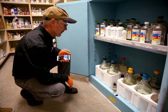 Chemistry safety consultant, Dave Waddell goes through a chemistry classrooms storage cabinet to make sure everything is up to date on Friday, Nov. 2 at West Salem High School.