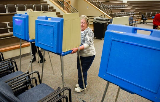 Election co-chair Gail Falconer positions  voting booths Monday, Nov. 5, for Ward 1 Precinct 3 at the St. Cloud City Hall.
