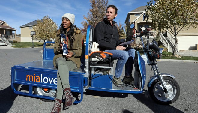 In this Saturday, Nov. 3, 2018, photo U.S. Rep. Mia Love, left, and her husband Jason look on during a get out the vote for Utah's 4th Congressional District in West Jordan, Utah. Love and her team climbed aboard a modified blue-and-orange motor scooter as they chatted with people mowing their lawns and heading to grocery stores. (AP Photo/Rick Bowmer)