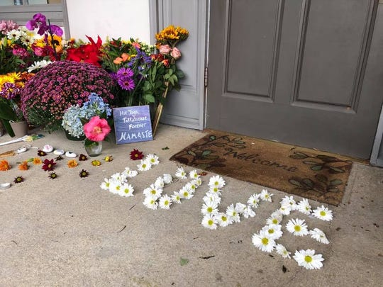 """The word """"love"""" is spelled out in daisies at the doorstep of Hot Yoga Tallahassee, where a fatal mass shooting two victims and the alleged shooter died at the business Friday evening."""