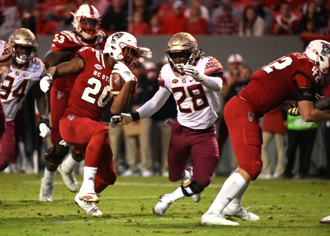North Carolina State Wolfpack running back Ricky Person Jr. (20) eludes Florida State Seminoles linebacker DeCalon Brooks (28) during the second half at Carter-Finley Stadium.  The Wolfpack won 47-28.