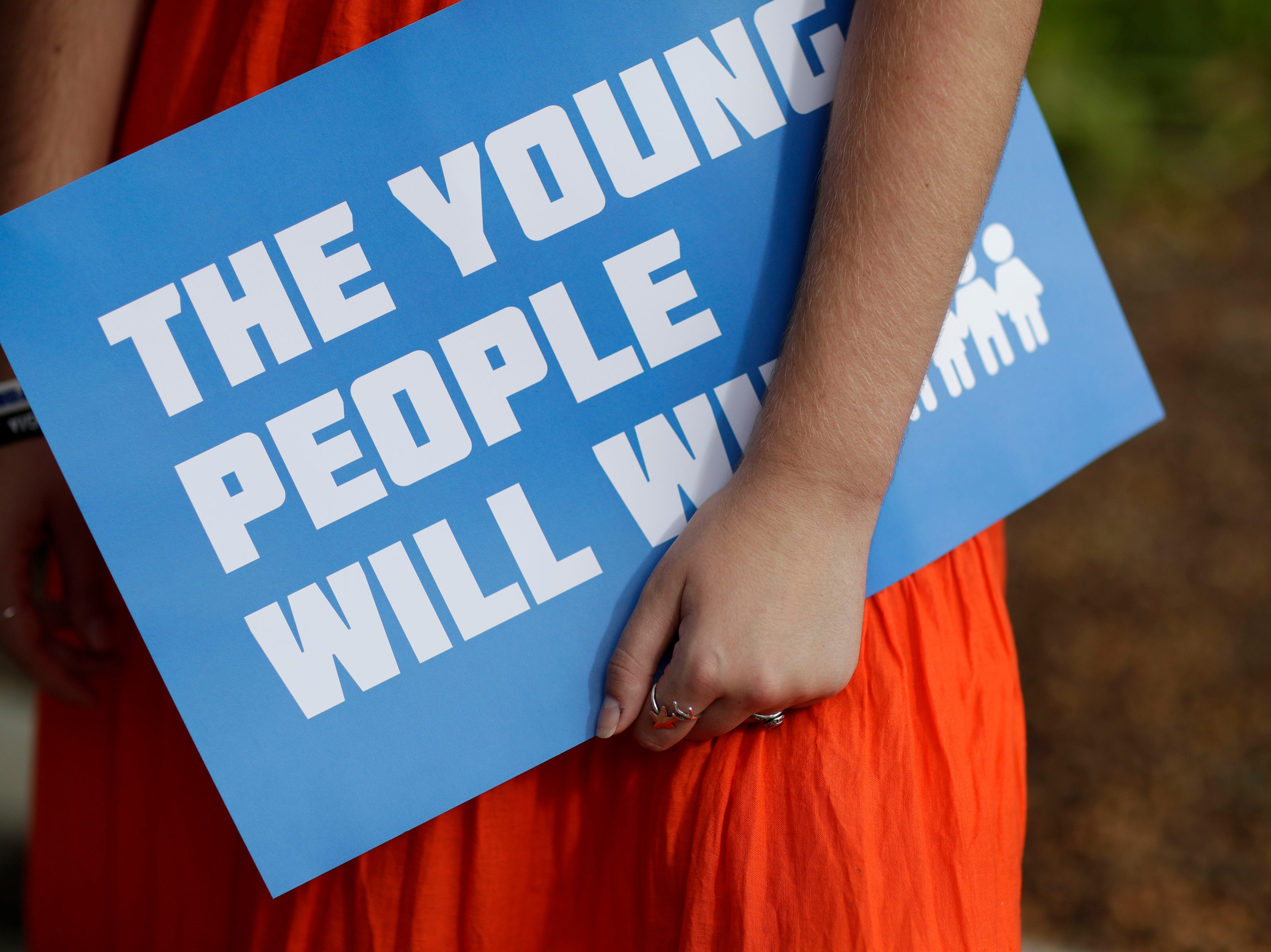 "Parkland shooting survivor and Marjory Stoneman Douglas graduate Delaney Tarr, 18, holds a sign saying ""the young people will win"" as she speaks to the press after appearing with the March for Our Lives movement during a press conference on the steps of the Florida Historic State Capitol in Tallahassee, Fla. Monday, Nov. 5, 2018 ahead of the 2018 midterm elections Tuesday."