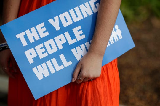 """Parkland shooting survivor and Marjory Stoneman Douglas graduate Delaney Tarr, 18, holds a sign saying """"the young people will win"""" as she speaks to the press after appearing with the March for Our Lives movement during a press conference on the steps of the Florida Historic State Capitol in Tallahassee, Fla. Monday, Nov. 5, 2018 ahead of the 2018 midterm elections Tuesday."""