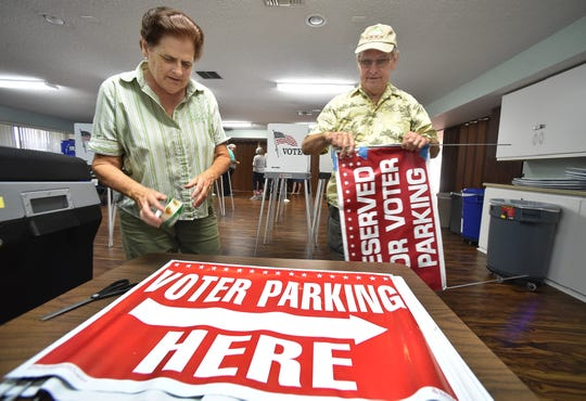 Poll workers Carolyn Berzinski (left) and her husband, Phil, of Vero Beach, repair precinct signs on Monday, Nov. 5, 2018.