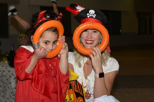 Henesis and physical therapist Geri Guercio play peek-a-boo with the ring toss rings at the Halloween party at PATCHES Prescribed Pediatric Extended Care facility in Fort Pierce.