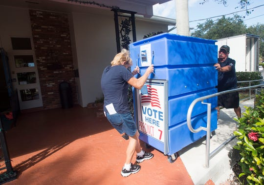 """A-1 Moving & Storage team Mary Rigdon (left) and Ron Merrill move a locked blue cart into Precinct 7 on Monday, Nov. 5, 2018, at the Woman's Club of Stuart. The cart weighs 300-400 pounds, according to Merrill, and houses all of the voters ballots. """"It's good that we can get out here and help the community,"""" Merrill said."""