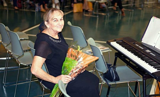 Gifford Youth Orchestra's Strings Program Music Director Joan Haar receives a bouquet of flowers at the orchestra's Crystal Concert on Nov. 3 at the Gifford Youth Achievement Center.