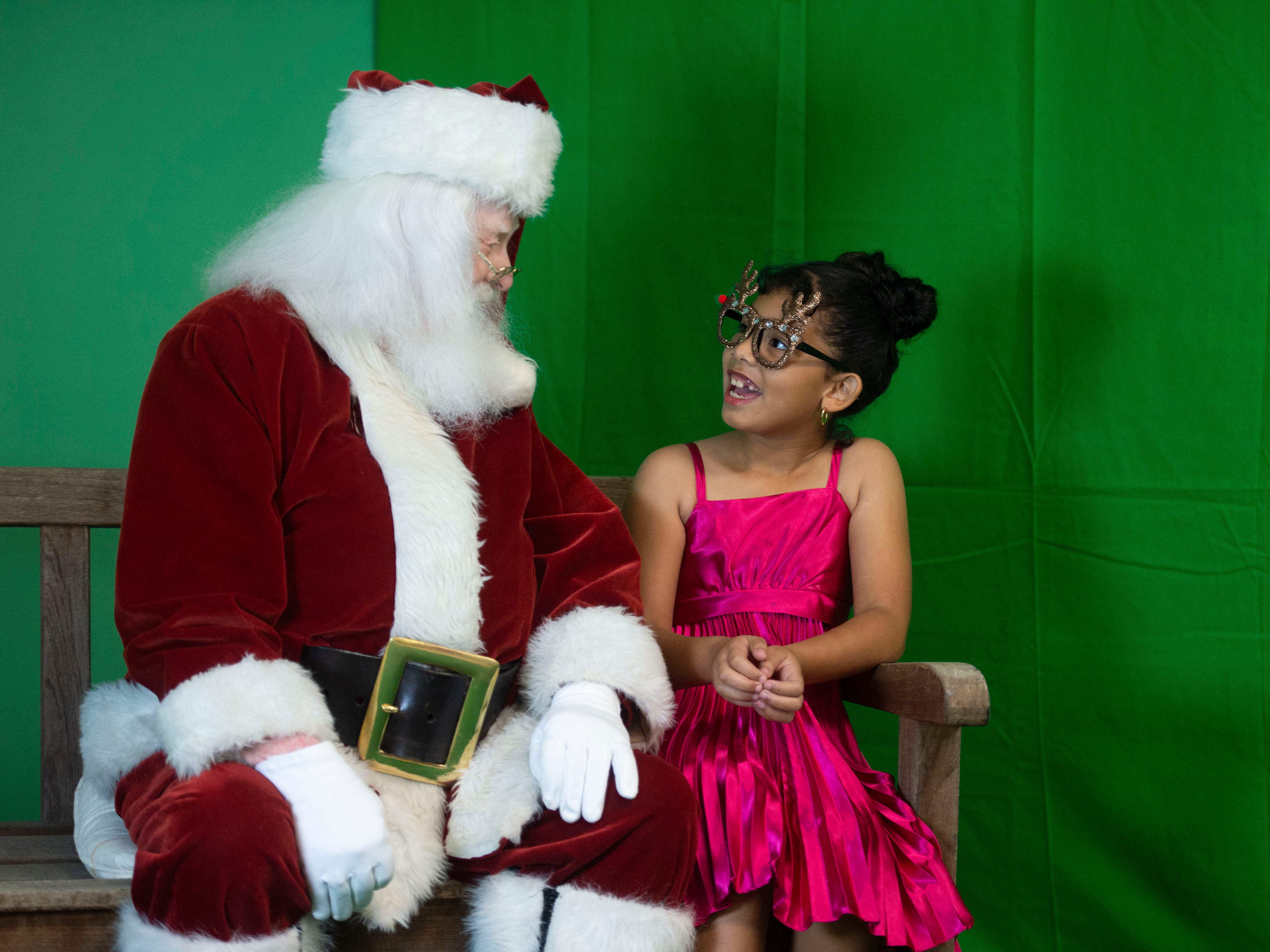"Veronica Colon, 8, of Vero Beach, shares a moment with Lance Willock, dressed as Santa Claus, during the Humane Society of Vero Beach and Indian River County's annual Santa Paws photo shoot Sunday, Nov. 4, 2018 at the Humane Society Thrift Store in Vero Beach. Willock is used to meeting children during the holiday season, but enjoys greeting the animals and helping out with the fundraiser. ""They're different than children but they all have personalities. Once they get acquainted with Santa it's interesting to see how they all react to Santa, almost like children somewhat,"" Willock said."