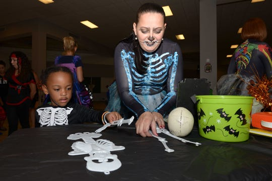 Anthony puts a skeleton together with Melina Torres at the Halloween party at PATCHES Prescribed Pediatric Extended Care facility in Fort Pierce.