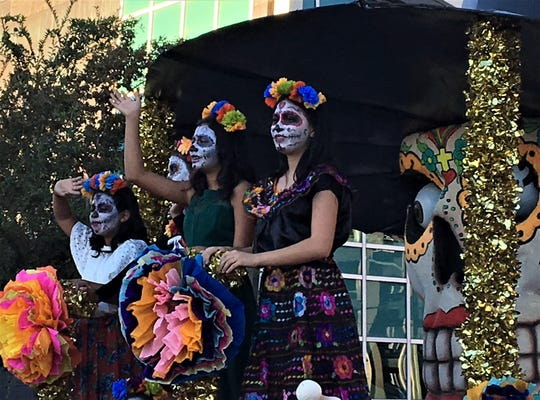 Girls in sugar skull makeup wave from a float in the  Dia de los Muertos 2018 parade in El Paso.