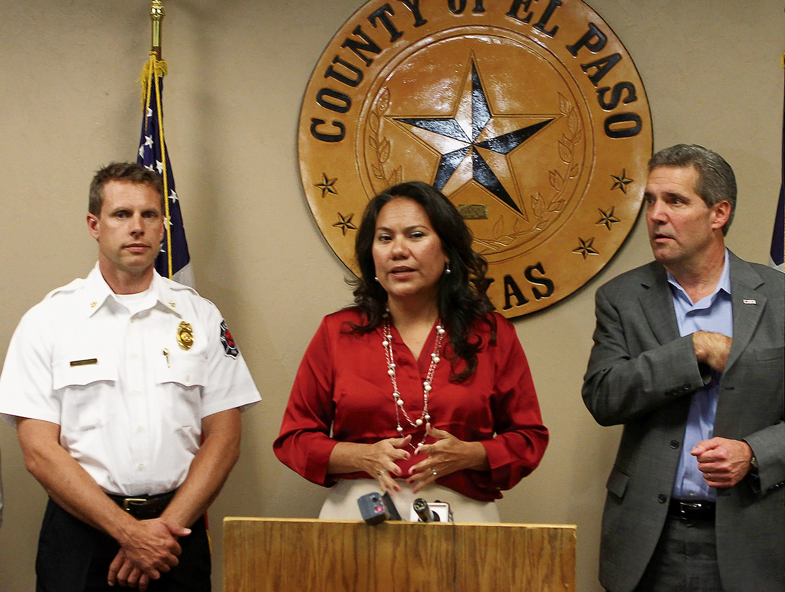 El Paso County Judge Veronica Escobar was flanked by El Paso Fire Dept. Deputy Chief Scott Calderwood, Emergency Management coordinator, left, and Mark Mathis of the American Red Cross Monday.