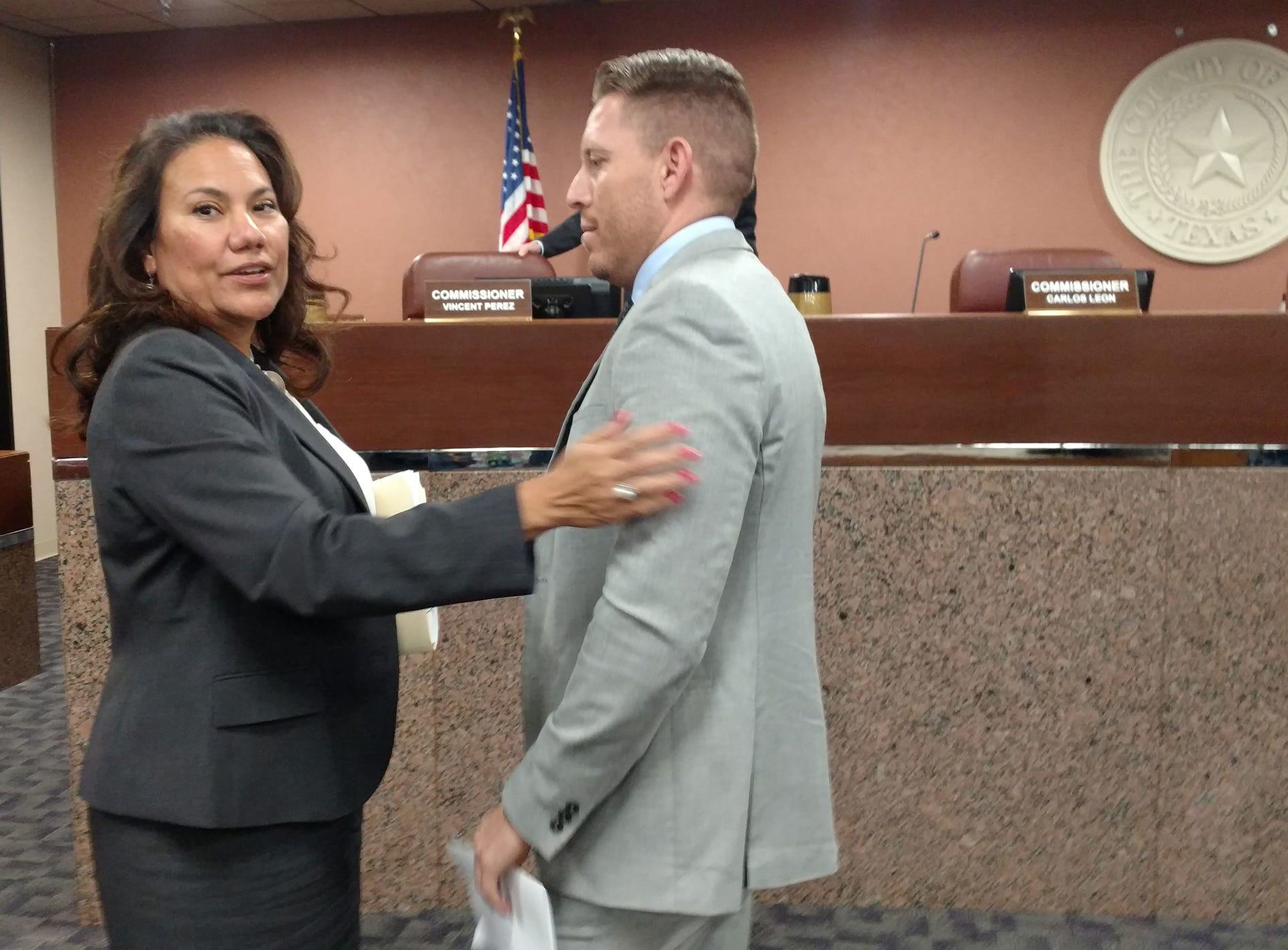 Outgoing County Judge Veronica Escobar talks to her replacement, Ruben Vogt, after county commissioners chose him 4-1 for the position.