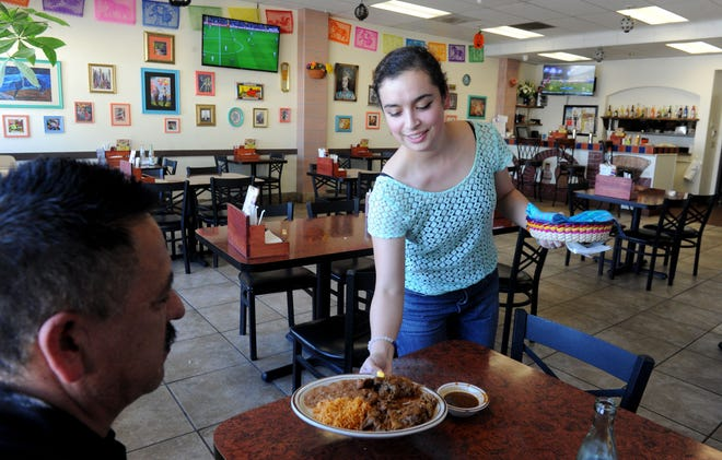 Waitress Rafaela Garcia serves Gabriel Gomez his birria de chivo combo plate at Fiesta Mexican Grill in Oxnard. The goat dish is one of the specialities of Fiesta Mexican Grill, which brings the flavors of Jalisco, Mexico, to Oxnard.