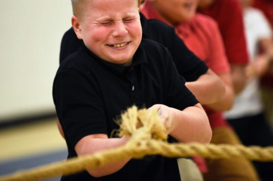 Sixth grader Dennis Ostapenko, 11, competes in a military themed game of four-way tug of war Monday, Nov. 5, 2018 at Lincoln Avenue School in Vineland, N.J.