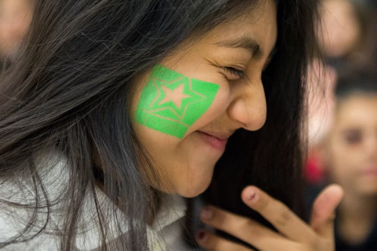 Janxin Reyes, 14, smiles with her US Army temporary tattoo as the school honors veterans Monday, Nov. 5, 2018 at Lincoln Avenue School in Vineland, N.J.