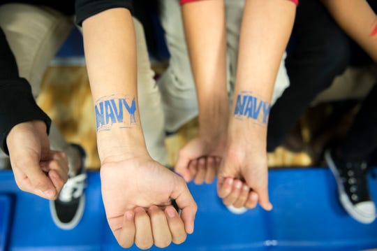 Students extend their arms as their Navy temporary tattoos dry Monday, Nov. 5, 2018 at Lincoln Avenue School in Vineland, N.J.