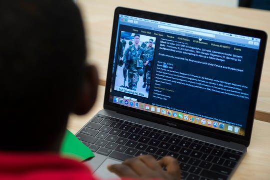 Theo Barclay, 14, works on his Veterans Day project as a photo of Sgt. Dominick M. Pilla is seen on his computer screen Monday, Nov. 5, 2018 at Lincoln Avenue School in Vineland, N.J.
