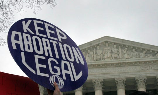 A pro-choice demonstrator holds a sign before the U.S. Supreme Court in Washington, D.C.  AFP/Getty Images