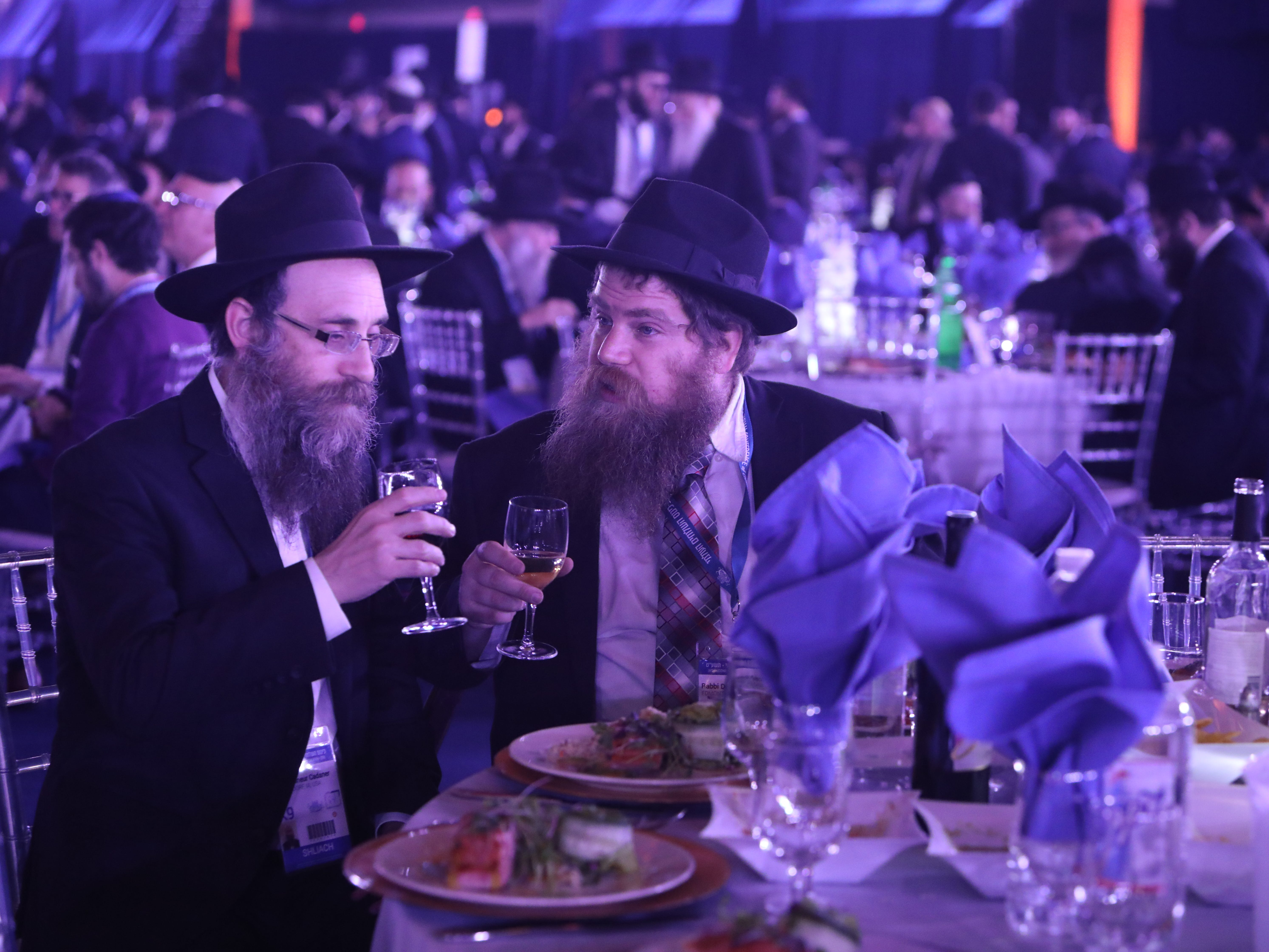 Rabbi Shneur Cadaner, left, of Bettendorf, Iowa and Rabbi Dovid Pinson of Edmonton, Canada attend a banquet at Rockland Community College Nov. 4, 2018 in Suffern, N.Y. They are among 5,600 rabbis and guests from 100 countries in New York for the International Conference of Chabad-Lubavitch Emissaries, an annual event aimed at strengthening Jewish awareness and practice around the world. This year's gathering comes only days after the anti-Semitic shooting in Pittsburgh which has been a focal point of the conference.