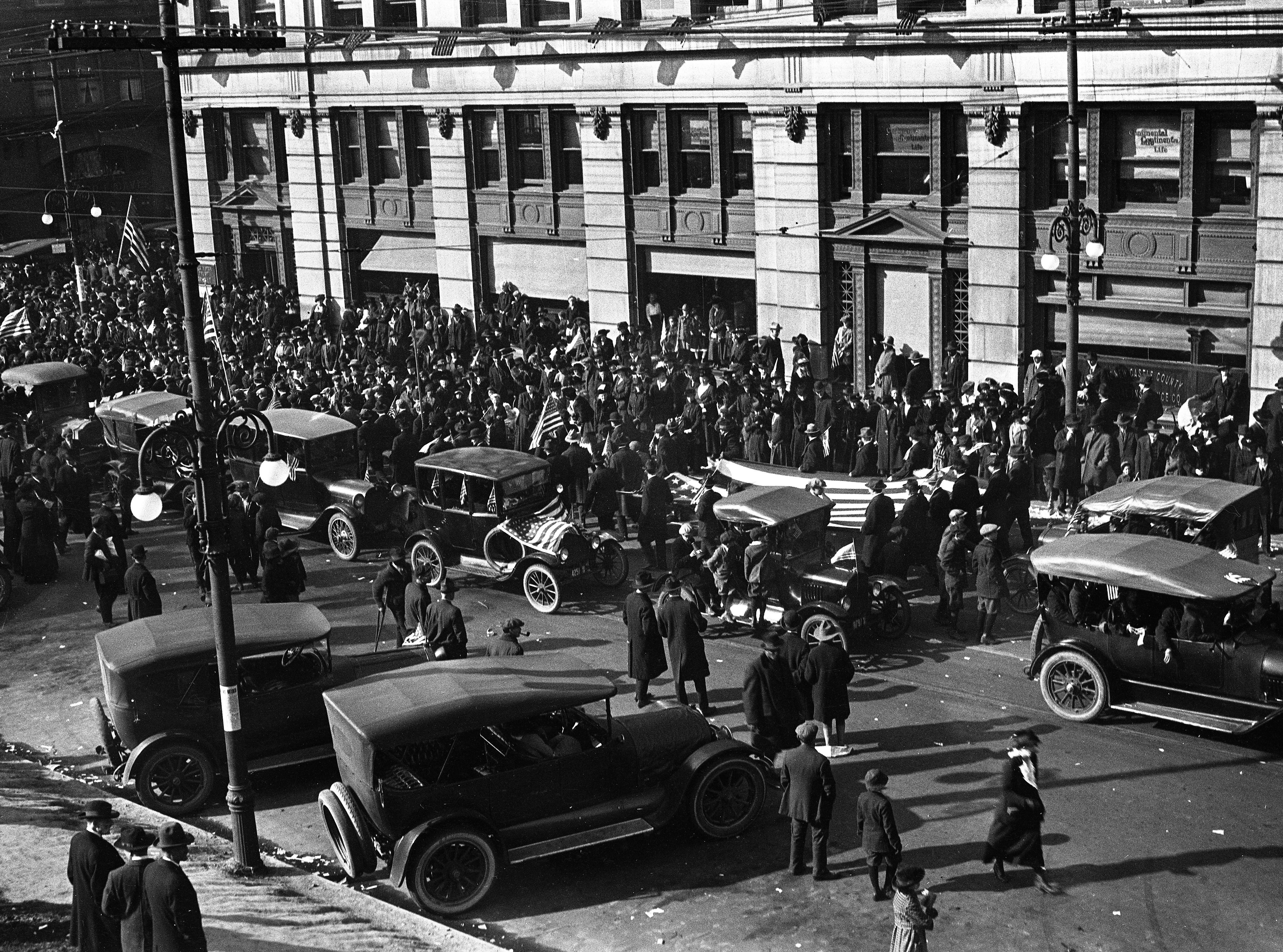 Scenes from the Wilmington Peace Parade after Armistice Day in 1918; crowds, cars and American flags in front of the du Pont building.