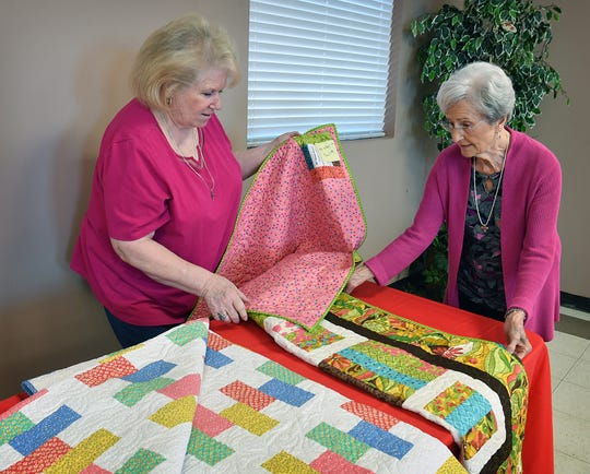 Sandy Reed, left, and Jean Salter talk about the two quilts made by Tracy Johnson that will be for sale Tuesday at the 90th Annual Election Day Soup Luncheon and Bazaar at the Church of the Good Shepherd.