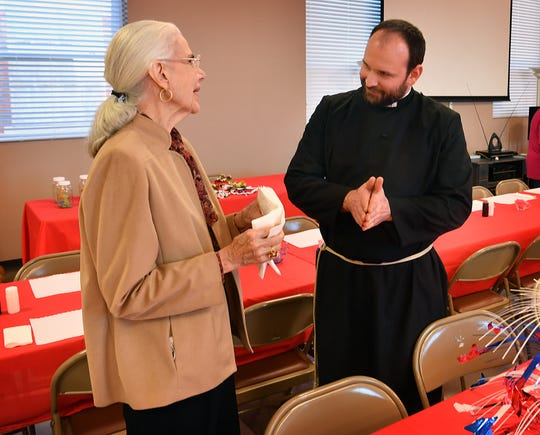 Father Brian Chase visits with Mary Styles as she helps set up for the 90th Annual Election Day Soup Luncheon and Bazaar at the Church of the Good Shepherd Monday morning.