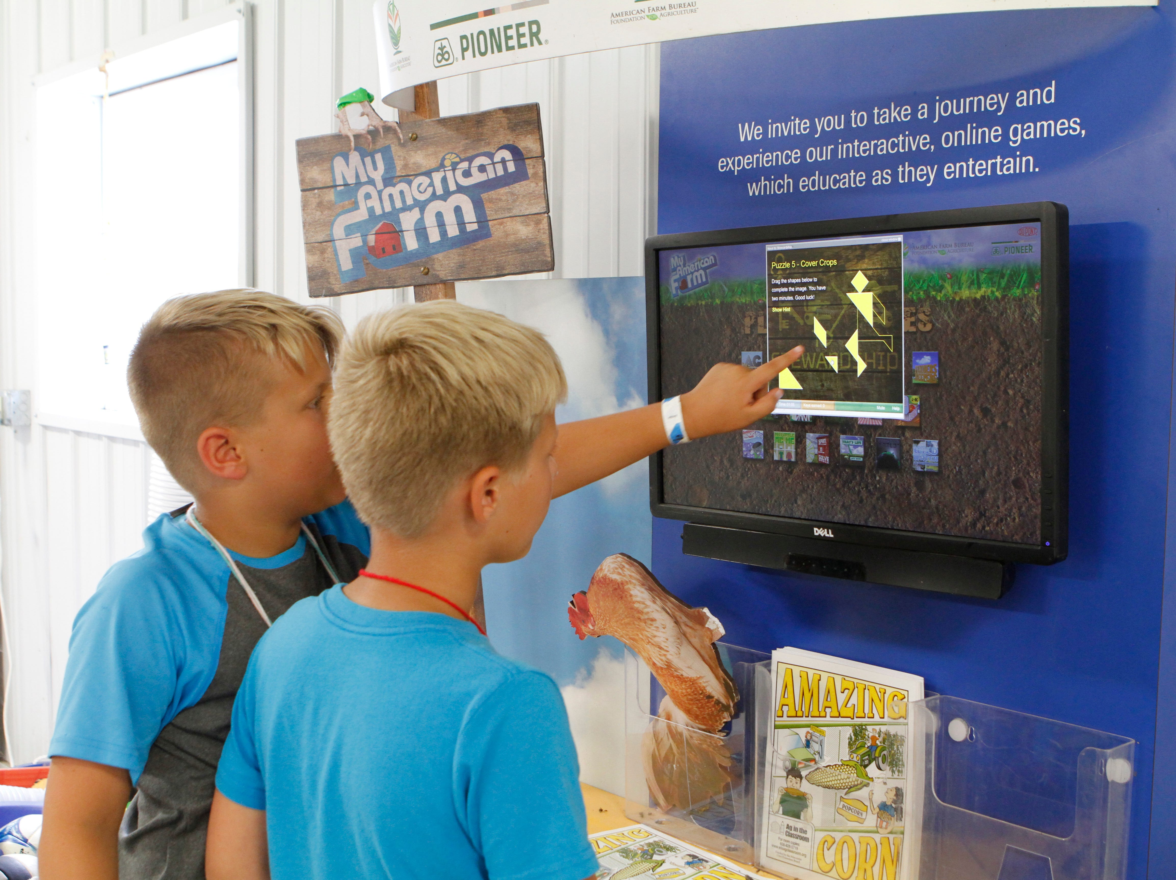 Tate (left) and Easton Nitschke, 9, play an interactive game on cover crops during a farm camp on Aug. 9 at Roden's Barnyard Adventures, West Bend.