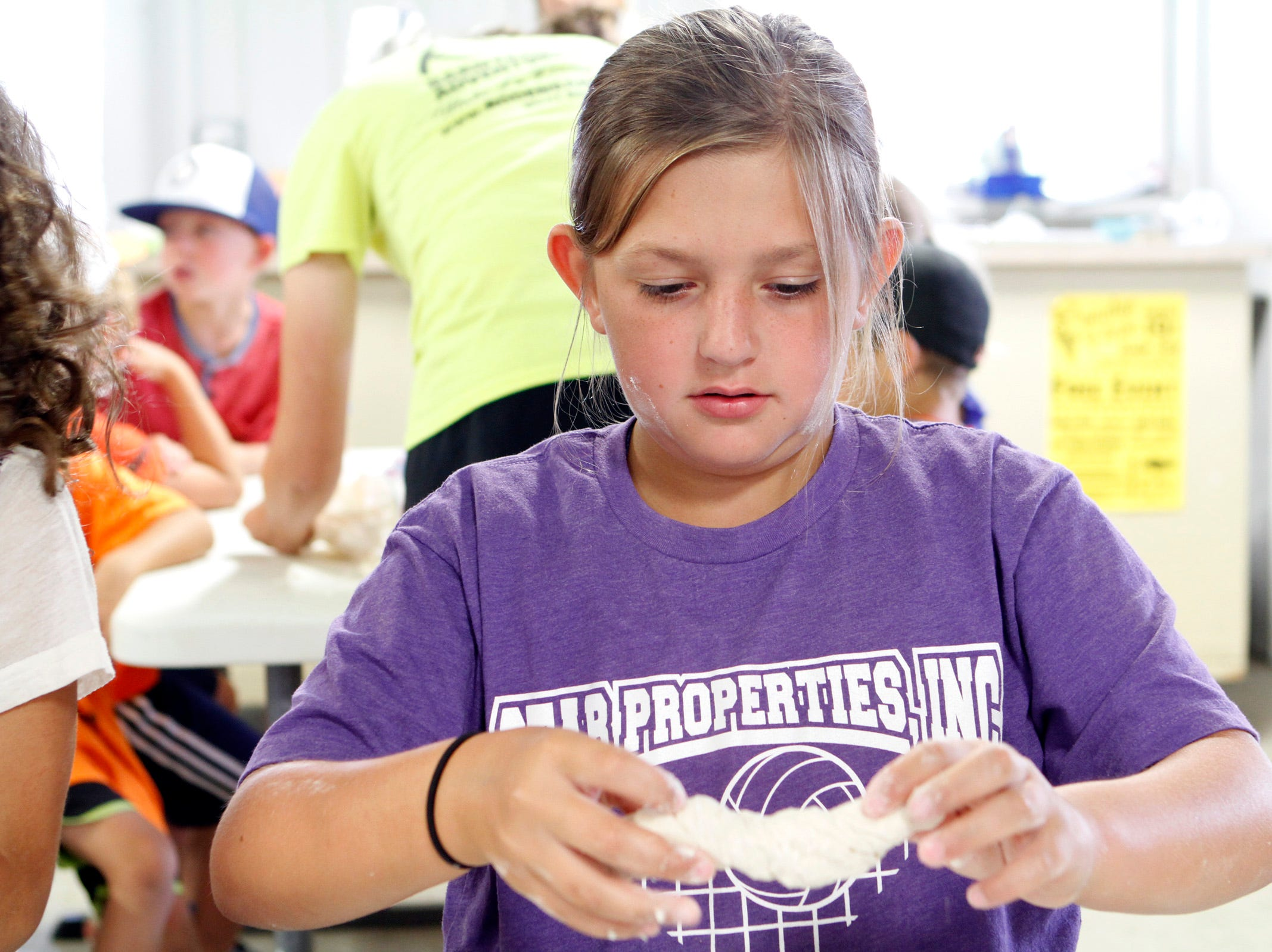 Alayna Cruss, 9, shapes a pretzel out of dough during a farm camp at Roden Barnyard Adventures in West Bend on Aug. 9.