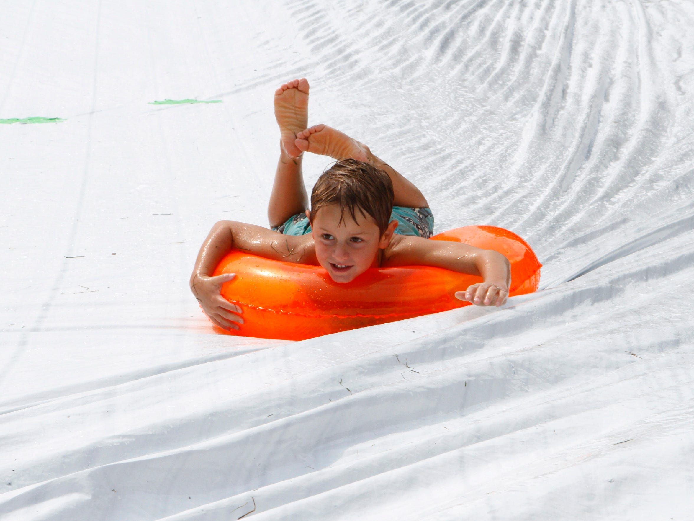 Tommy Bibo cruises down a giant slip and slide at Roden Barnyard Adventures on Aug. 9.